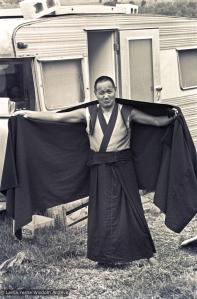 Lama adjusts his robe, 1975